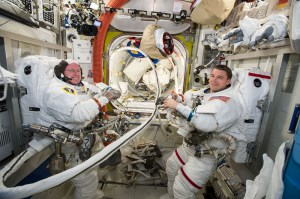 Astronauts Barry Wilmore, left, and Reid Wiseman set up their space suits and tools in the equipment lock of the Quest Airlock aboard the International Space Station on October 1. Wilmore earned his master's in aviation systems from UT.