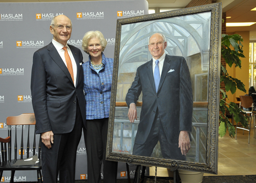 Jim and Natalie Haslam stand next to a commissioned portrait of Jim Haslam's likeness