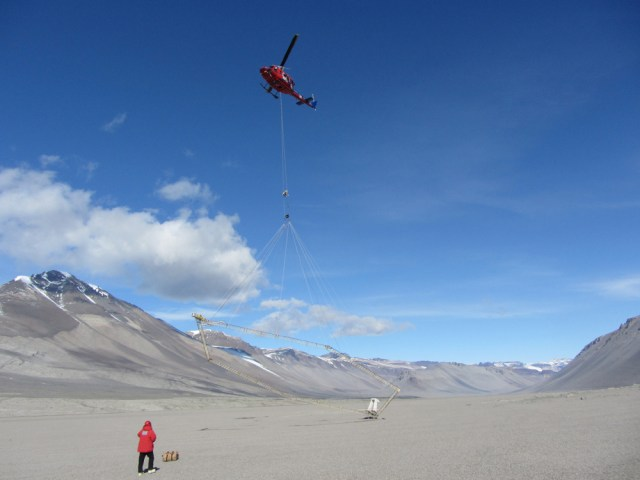 A helicopter begins a survey with the airborne electromagnetic sensor at Bull Pass in the Wright Valley, McMurdo Dry Valleys, Antarctica. (Credit: J. Mikucki)