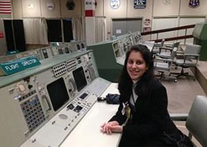 Carol Miselem in the Apollo-era flight director seat at Johnson Space Flight Center in Texas.