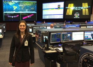 Justine Barry stands next to the current flight director's seat at Johnson Space Flight Center in Texas.