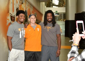 Noah Hays, center, poses for a photo with football players Todd Kelly Jr., left, and Jalen Reeves-Maybin, right, while touring Athletics facilities.