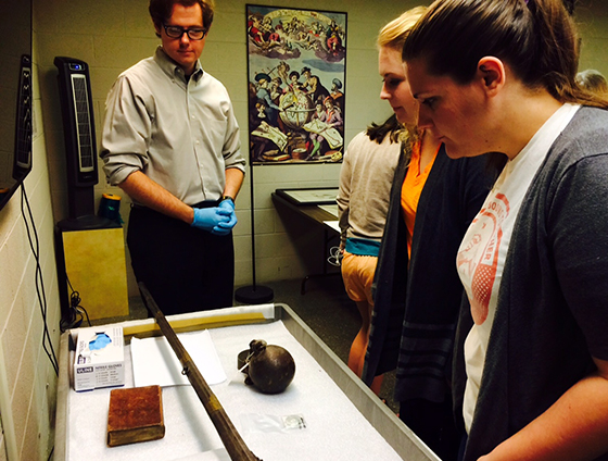 Robert Rennie from the McClung Museum presents a ball and chain shackle (1706), a gun (1702), and a copy of The Wealth of Nations from the museum's special collections to a class studying a 1688 novella about the slave trade.
