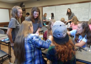 """UT engineering students (in gray shirts) help area middle and high school students during 2015's """"Tomorrow's Engineers Today"""" event. UT's chapter of the Society of Women Engineers (SWE) helps stage the event, with backing from Eastman."""