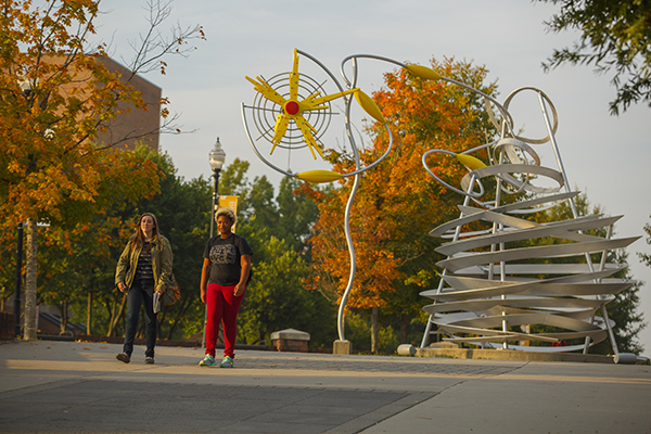 Two female students walking on the Joe Johnson and John Ward Pedestrian Walkway by the sculpture A Startling Whirlwind of Opportunity by Alice Aycock. Photography by FJ Gaylor Photography.