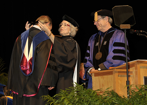 Chancellor Jimmy G. Cheek is presented with the chancellor's medal by Andrea Loguhry during his investiture while Interim President Jan Simek looks on.