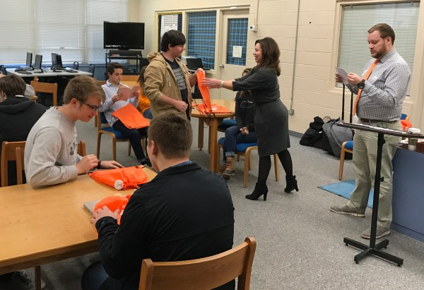 Tyler Lewelling and Elizabeth Dixon pass out admit packets and some orange swag to Gatlinburg-Pittman admitted seniors.