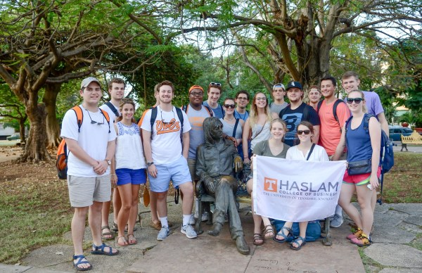 Members of the 2016 First Year Experience in Cuba class pose in a park in Havana with a Haslam College of Business flag.
