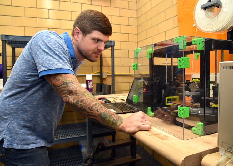 Navy Veteran, and former  Navy Diver Alex Weber working in the College of Engineering 3 D modeling lab creating a prosthesis hand.