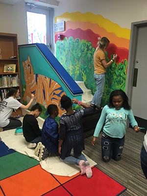 UT students Jacqueline Wright (left) and Kayla Duncan (top) work with students in kindergarten through second grade to complete a mural in the Maynard Elementary School library.