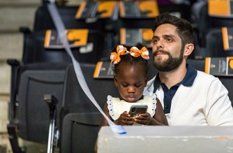 Country music artist Thomas Rhett holds his adopted daughter Willa Gray, age 2, as his wife Lauren Akins, a 2012 BSN graduate, delivers the keynote address to graduates of the University of Tennessee's College of Nursing during their commencement at Thompson-Boling Arena on Saturday, May 12, 2018. ..Photo by Erik Campos