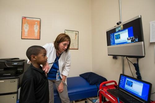 Jennifer Hoskins using telehealth system to communicate with Nan Gaylord at VSHC