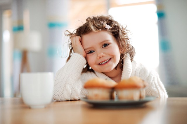 A portrait of small girl sitting at the table at home, eating muffins.