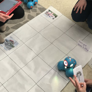 Children use a robot to navigate a gridded map of their community.