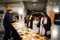 Graduates get their name cards from a table inside Thompson-Boling Arena before being seated.