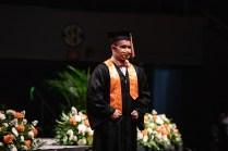 A graduate in an orange bowtie walks across the stage.