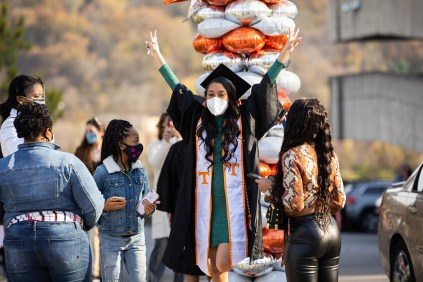 A graduate celebrates outside Thompson-Boling Arena, holding up two peace signs.