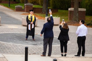 A graduate takes photos on the Seal
