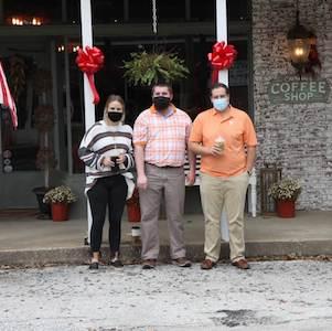 Garland, R.T. McBride, and Ankar outside Corner Coffee Shop in Loretto, Tennessee.