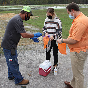 UT students Kendall Garland (center) and Noah Ankar collect a sample at Loretto Waste Water Plant.