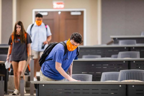 Students use disinfectant wipes to clean their desk while participating in a setup photoshoot portraying what student life will look like while wearing a mask and social distancing inside Strong Hall on July 10, 2020. Photo by Steven Bridges/University of