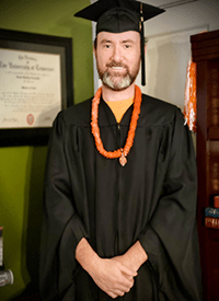 David Leventhal in graduation regalia stands next to his framed Master of Secondary Education degree.