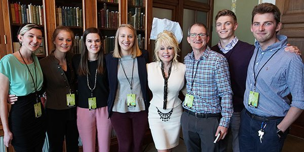 six students pose with Dolly Partoon