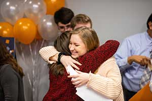 Emma Heins hugs a friend after being surprised with the Torchbearer Award.