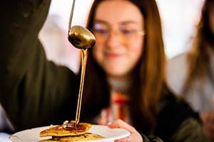 Student pours syrup on a pancake.