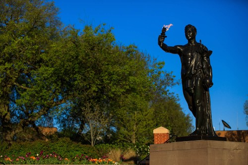 Spring flowers bloom around the Torchbearer in Circle Park on the evening of