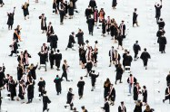 Graduates embrace on the field after their commencement ceremony.