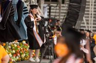 A graduate makes a heart with her hands as she crosses the stage at commencement.