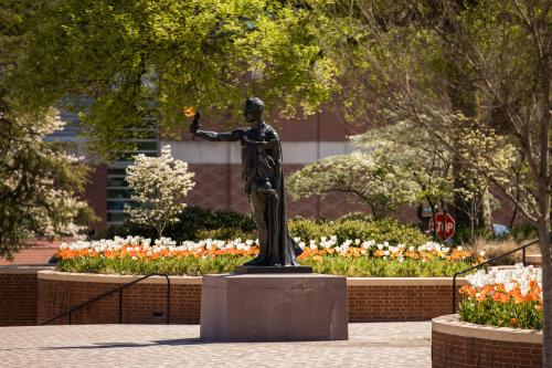 The Torchbearer Statue stands tall as spring flowers bloom in