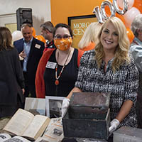 Alesha Shumar, right, assistant head and university archivist with the Betsey B. Creekmore Special Collections, and senior library associate Rebecca Becker display the 1919 time capsule and duplicates of the contents that were placed inside it.