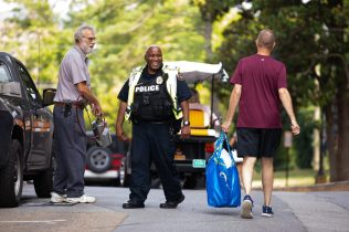A UTPD officer chats with a facilities services employee and a parent of an incoming student on move-in day.