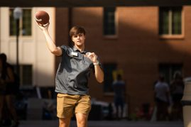 A resident assistant passes a football with an incoming new student between move-in appointments.