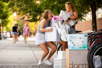 Two new students laugh as they juggle boxes to move into their residence hall.