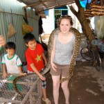 Danielle Gerhard is draped with a python in a market in Vietnam's Mekong Delta