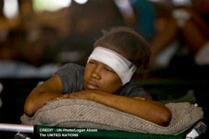 A Haitian girl rests after receiving treatment at an ad hoc medical clinic