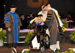 Inskip Elementary School Principal Elisa Luna receives her doctoral hood from Robert Kronick, professor of education psychology and counseling, at a ceremony on May 12, 2011, at the University of Tennessee, Knoxville. Looking on is Bob Rider, dean of the College of Education, Health, and Human Sciences. Luna was paralyzed after she was shot by a disgruntled teacher at Inskip in February 2010.
