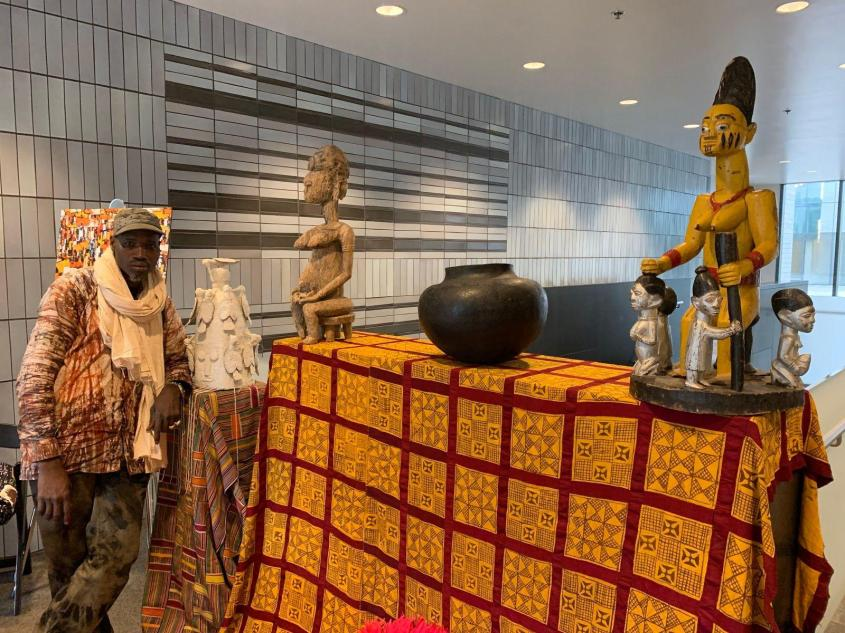 "Diarra Diaby stands next to collected pieces. From left: a ceremonial Yoruba crown, ""Mother and Son"" statue, South African cooking pot and ""Queen Mother"" statue. (Angel Idowu / WTTW News)"
