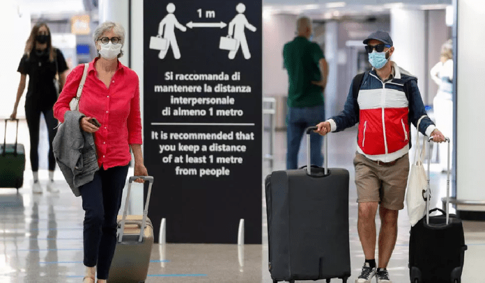 Passengers wearing protective face masks walk at Fiumicino Airport in Rome, Italy. photo by Guglielmo Mangiapane, REUTERS