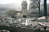 A chimney stands amid burned rubble of a structure.