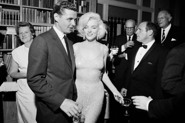 "In this May 19, 1962 photo provided by the John F. Kennedy Presidential Library and Museum, actress Marilyn Monroe wears the iconic gown that she wore while singing ""Happy Birthday"" to President John F. Kennedy at Madison Square Garden, during a reception in New York City. Standing next to Monroe is Steve Smith, President Kennedy's brother-in-law. Julien's Auctions will offer Monroe's gown at auction in Los Angeles on Nov. 17, 2016. (Cecil Stoughton/White House Photographs, John F. Kennedy Presidential Library and Museum via AP)"