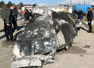 People standing and analysing the fragments and remains of the Ukraine International Airlines plane Boeing 737-800 that crashed outside the Iranian capital Tehran
