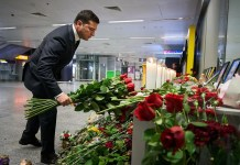 President Volodymyr Zelensky placing flowers at a memorial for the victims of the Ukraine International Airlines Boeing 737-800 crash in the Iranian capital Tehran, at the Boryspil airport outside Kiev