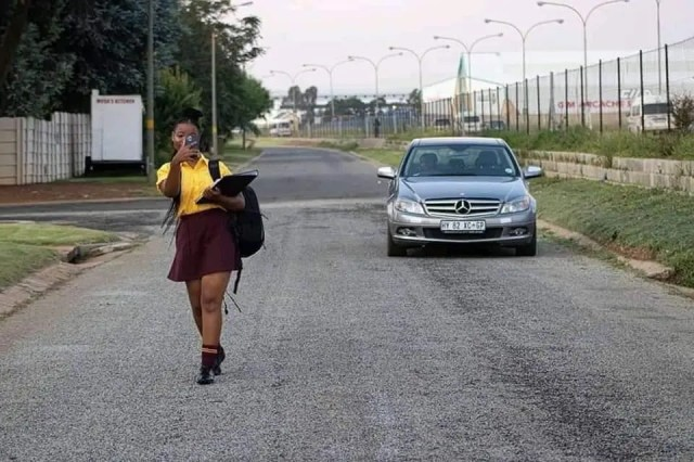 Man in Mercedes Benz picks student