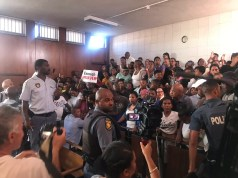 Angry community members look to force way into court