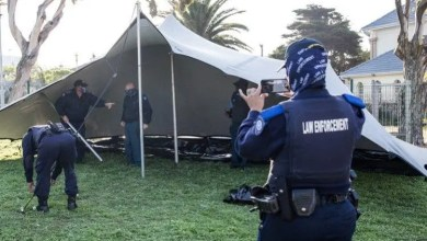 City of Cape Town law enforcement officers removing one of the marquees on the Village Green