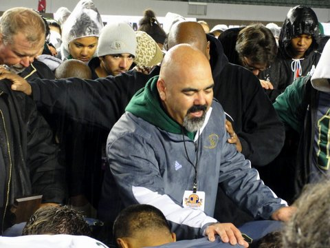 Long Beach Poly High School football coach Raul Lara leads his team and the Granite Bay Grizzlies in prayer for the school shooting victims in Newtown, Connecticut shortly after the California Division I State Championship football game in Carson, California. Photo Credit: Dennis J. Freeman